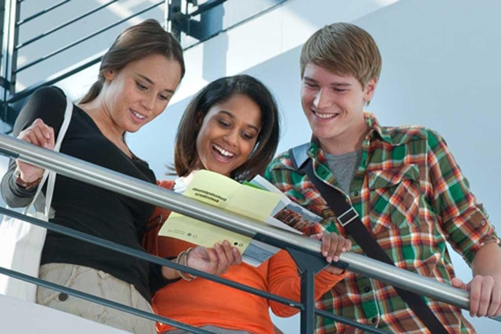 Bild von drei Jugendlichen, die eine Broschüre lesen