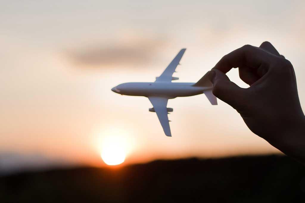 Spielzeugflugzeug, das in den Sonnenuntergang gehalten wird