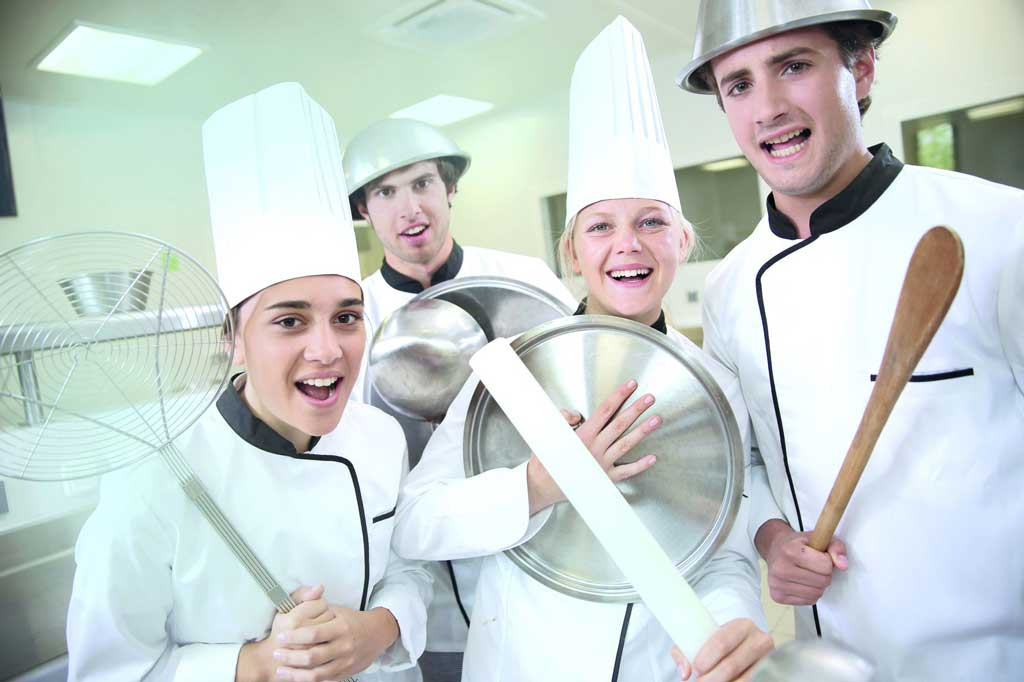 Vier Jugendliche in Küchenkleidung mit Kochutensilien