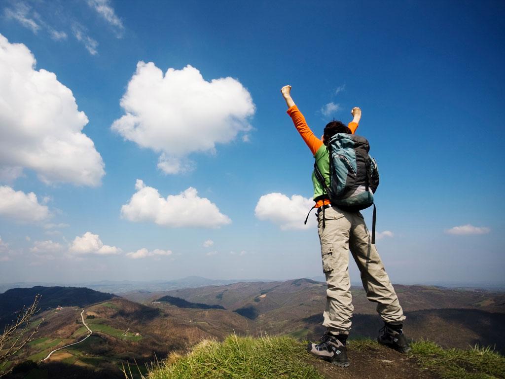 Wanderer auf einem Berg streckt die Arme in die Luft